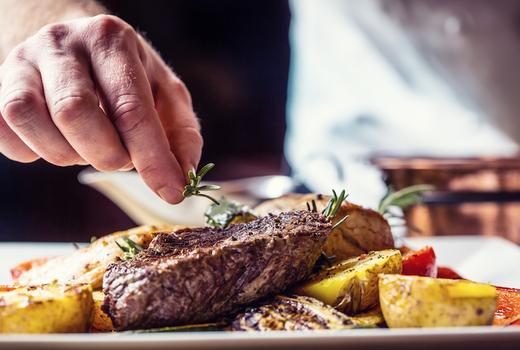 Mykonos grill dinner chef hand seasoning potatoes