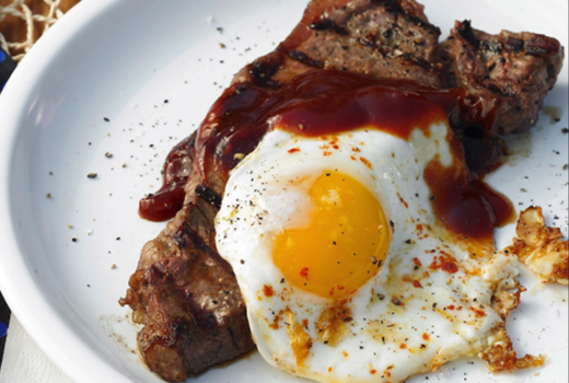 Steak eggs sauce white plate